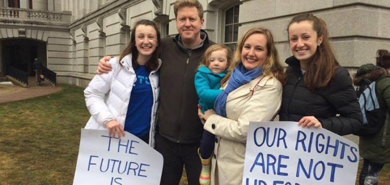 Kelda and family smiling at the women's march on Madison